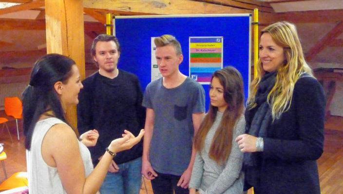 Azubi Pia Aufinger (links) im Gespräch mit Schülern der Klasse 10z, rechts ist Lehrerin Nina Wagner zu sehen.