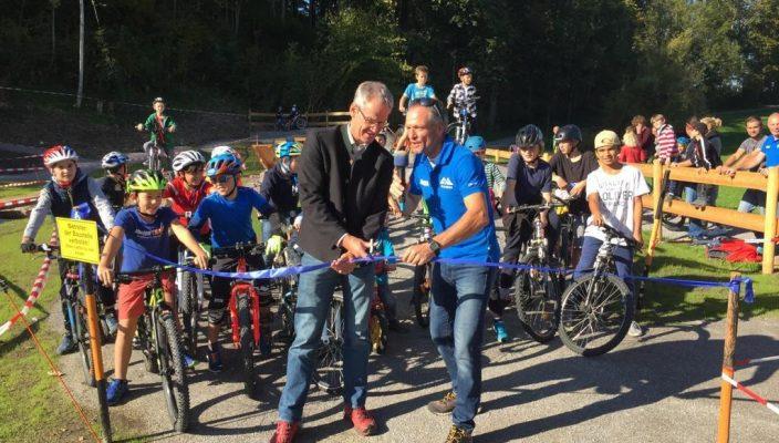 Bürgermeister Matthias Jokisch, links, und Michael Maier bei der offiziellen Eröffnung des neuen Bikeparks. Die Kids im Hintergrund in Startposition. Foto: www.toponmountain.com