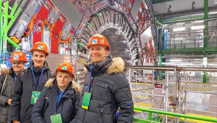 Von links: Vor der Weltmaschine CMS: Benedikt Schiller und Ferdinand Pelzl, Klasse 9a, umrahmt von StR Franziska Frank und StD Florian Ludwig.