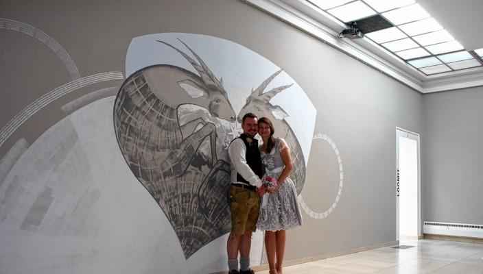 Das Ehepaar Graef freut sich vor dem Werk des Graffiti-Künstlers Loomit über ihre Eheschließung.