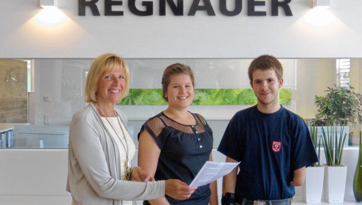Monika Hofmann (bfz) und Theresa Hagenauer (Firma Regnauer) überreichen Lukas S. den Ausbildungsvertrag (von links).