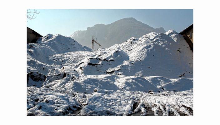 Fotografie von Robin Gordon: Aushub auf der Baustelle der ehemaligen Karfreitkaserne in Brannenburg vor der Silhouette echter Berge.