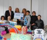 Karstadt Chef Matthias Ecke und die Erzieher Heidi Blank und Matthias Burchardt freuen sich mit Kindern von der Schönen Aussicht über die vielen Geschenke.