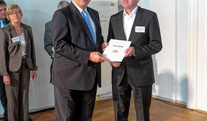 Joachim Herrmann, Staatsminister des Innern, für Bau und Verkehr, überreicht Baudezernent Helmut Cybulska die Urkunde für die Stadt Rosenheim.