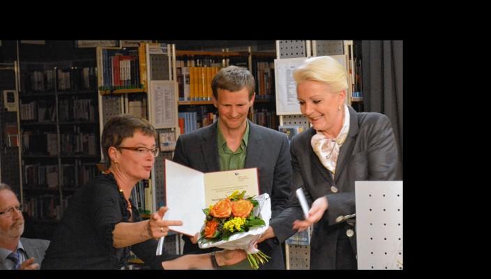 Oberbürgermeisterin Gabriele Bauer (rechts) und Bibliotheksleiterin Susanne Delp überreichen den Literaturpreis an Christian Lorenz Müller. Foto: Sieberath