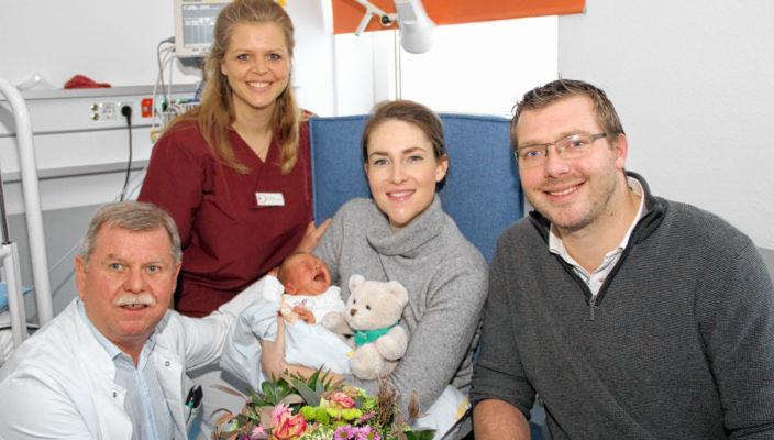 Familienglück: Die Eltern Paula und Peter Branscheid mit dem kleinen Julian. Mit einem Blumenstrauß und einem Teddybären gratulierten Dr. Manfred Lang, leitender Oberarzt der Klinik für Gynäkologie und Geburtshilfe (links), und Hebamme Sandra Aumer.
