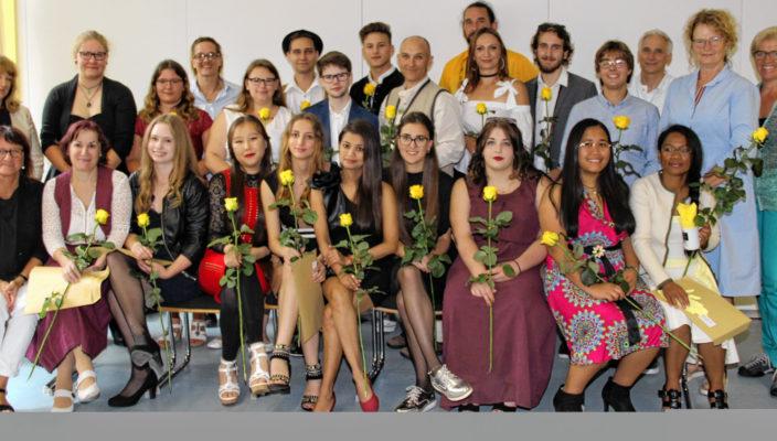 Lehrer, Ehrengäste und Absolventen freuen sich über den erfolgreichen Abschluss.