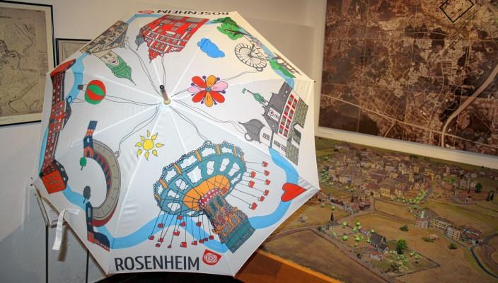 Diesen schönen Regenschirm zieren verschiedene Rosenheimer Wahrzeichen, darunter auch das beliebte Kettenkarussell.