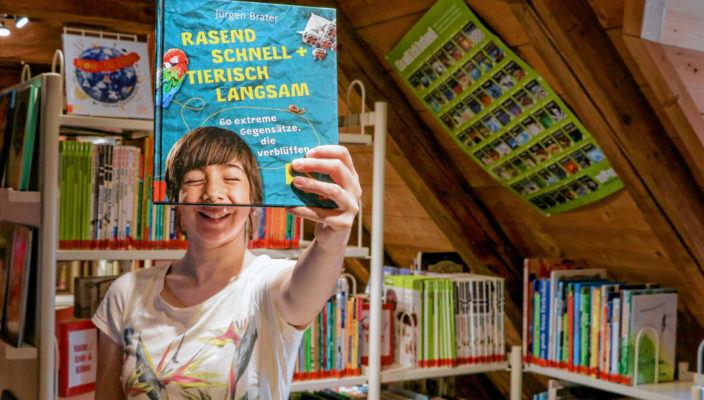 """Bei der digitalen Schnitzeljagd müssen beispielsweise bestimmte Bücher in den Regalen gefunden werden und mittels Foto dokumentiert werden. Büchereileiterin Bernadette Binder hat die Actionbound-App bereits getestet und ein kreatives """"Selfie"""" geschossen."""