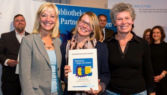 Monika Hochmuth und Gabriela Schmidt von der Stadtbibliothek freuen sich über die Auszeichnung und nehmen die Urkunde von Kultusstaatssekretärin Carolina Trautner entgegen.