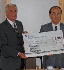 Bürgermeister Hiroshi Okubo (rechts) und der Vorsitzende des Fördervereins Udo Satzger bei der Scheckübergabe im Rathaus Rosenheim. Foto: Trux