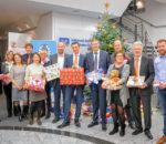 Mit vereinten Kräften Kindern ein Lächeln ins Gesicht zaubern: Vertreter von Round Table 99, vom Sozialdienst Katholischer Frauen und von der Volksbank Raiffeisenbank Rosenheim-Chiemsee eG freuen sich über die zahlreichen Geschenke.